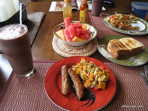 Smoothie, eggs, sausage, and fruit