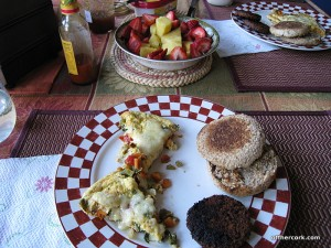 Eggs, english muffin, sausage, and fruit