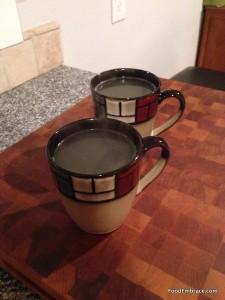 Mugs of chicken broth
